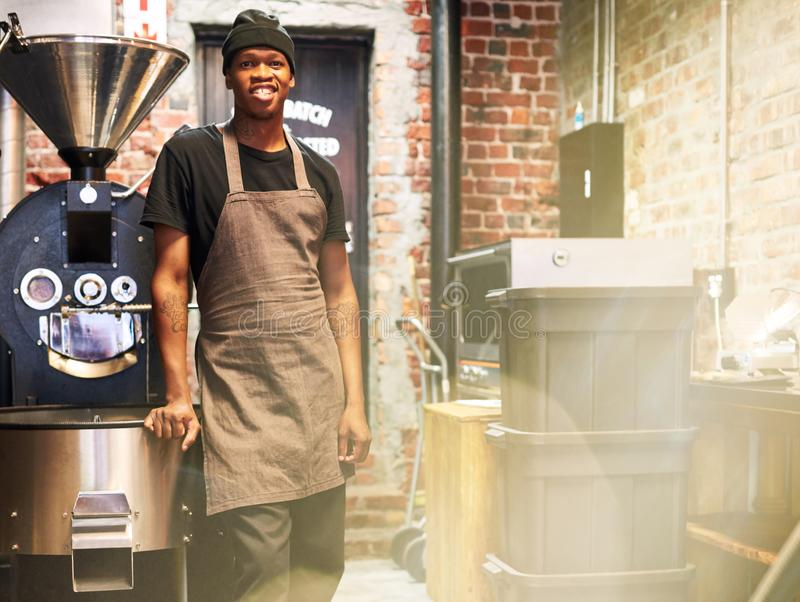 Afrikansk anställd som ler på kameran i grilla för kaffe, shoppar fotografering för bildbyråer