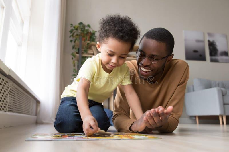 Afrikansk fader och litet för son pussel mot efterkrav hemma royaltyfria bilder