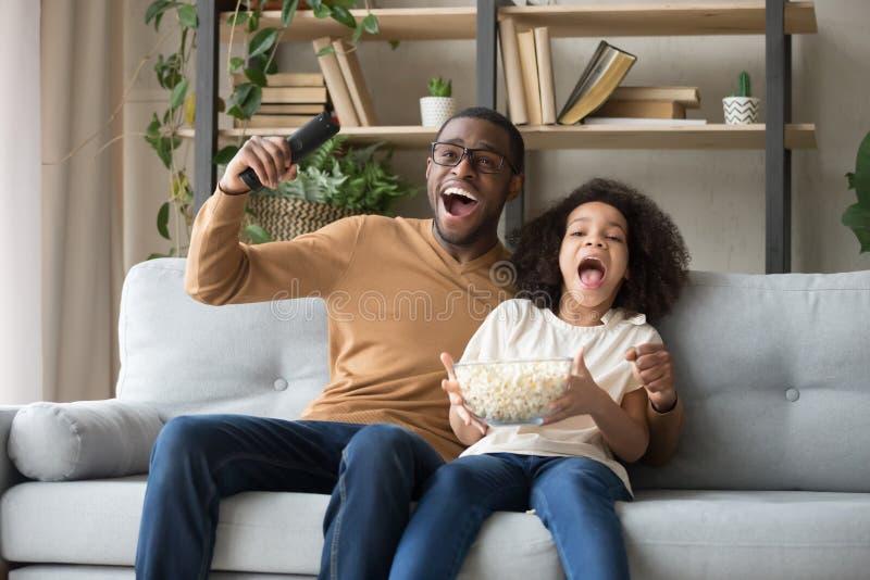 Afrikansk faderdotter som sitter på soffan som firar fotbollslagseger arkivbild