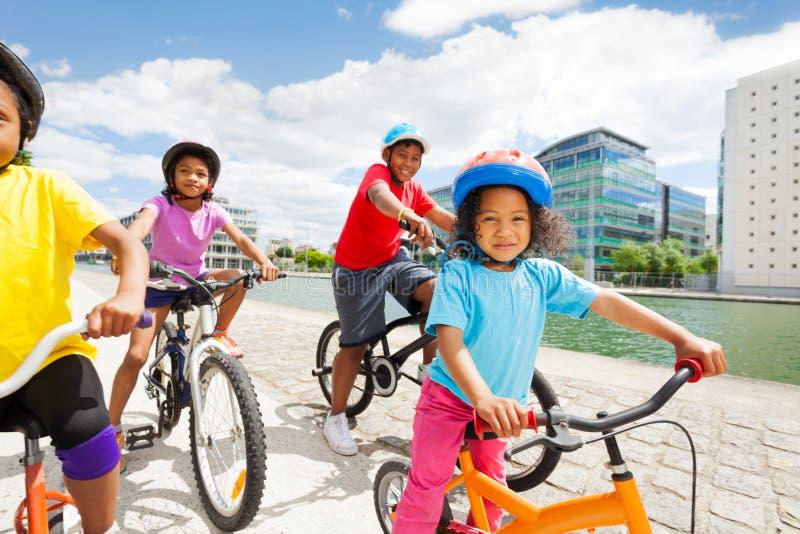 Afrikansk flicka i säkerhetshjälm som cyklar med vänner arkivfoto