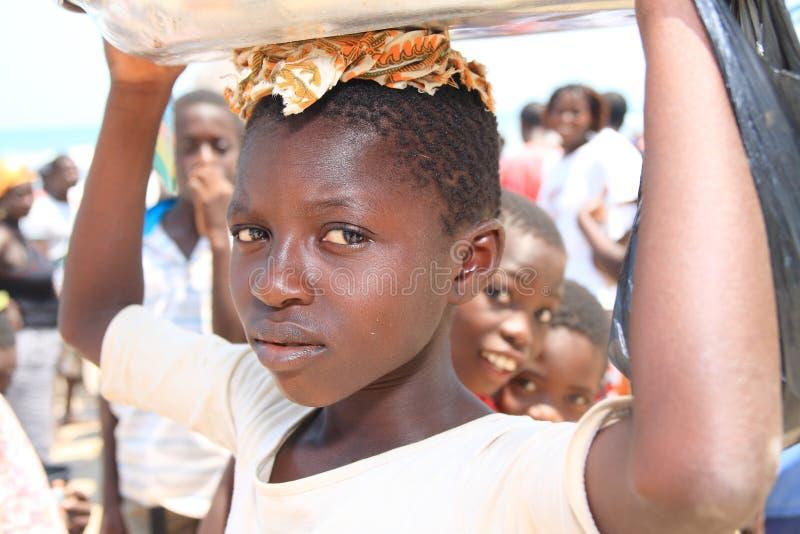 Afrikansk flicka med en bunke som är full av fisken, Ghana arkivfoto