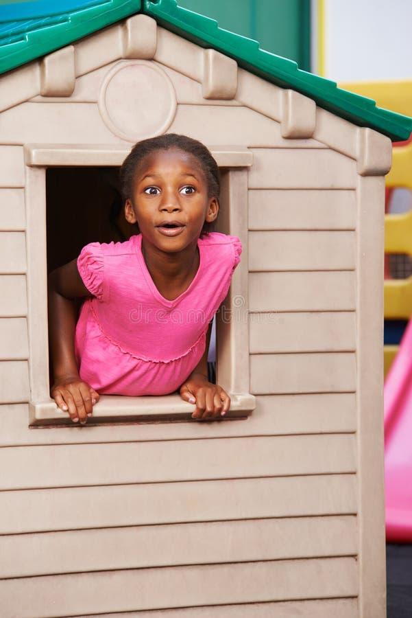 Afrikansk flicka som ser till och med fönster i lekstuga arkivfoto