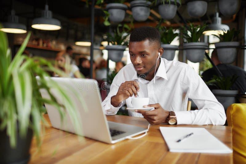 Afrikansk freelancerman som dricker kaffe som arbetar på kafét med bärbara datorn royaltyfri bild