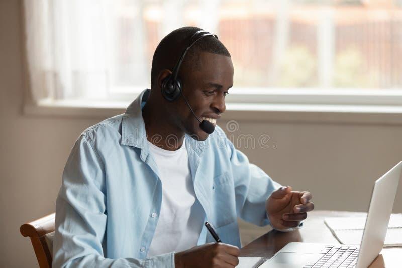 Afrikansk grabbkläderhörlurar med mikrofon som gör anmärkningar som studerar direktanslutet genom att använda datoren fotografering för bildbyråer