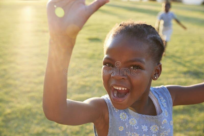 Afrikansk grundskolaflicka som utomhus vinkar till kameran royaltyfri bild