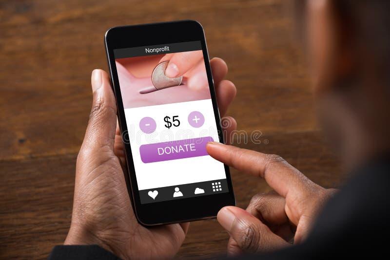 Afrikansk hållande mobiltelefon för affärsman som donerar pengar royaltyfri bild
