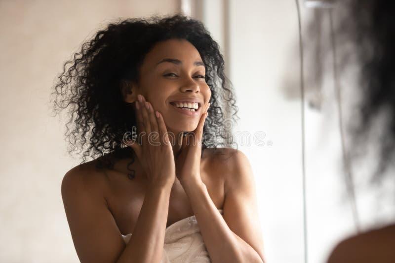 Afrikansk kvinna efter duschblick i spegeln som trycker på försiktig hud royaltyfria foton