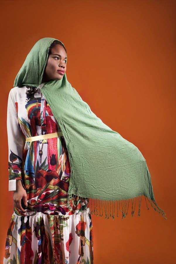 Afrikansk kvinna i halsduk och ljus klänning på orange bakgrund arkivbild