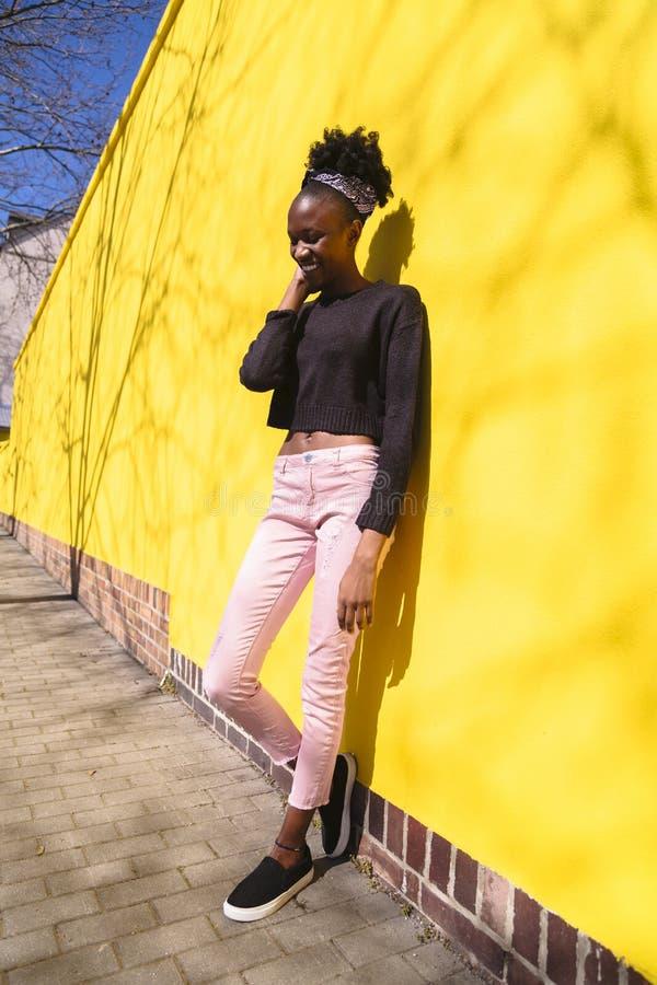 Afrikansk kvinna i jeans och tröja nära väggen arkivfoto