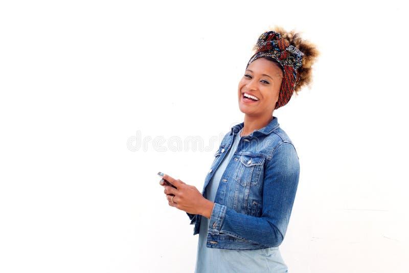 Afrikansk kvinna med smart telefonanseende mot vitt bakgrund och skratta fotografering för bildbyråer