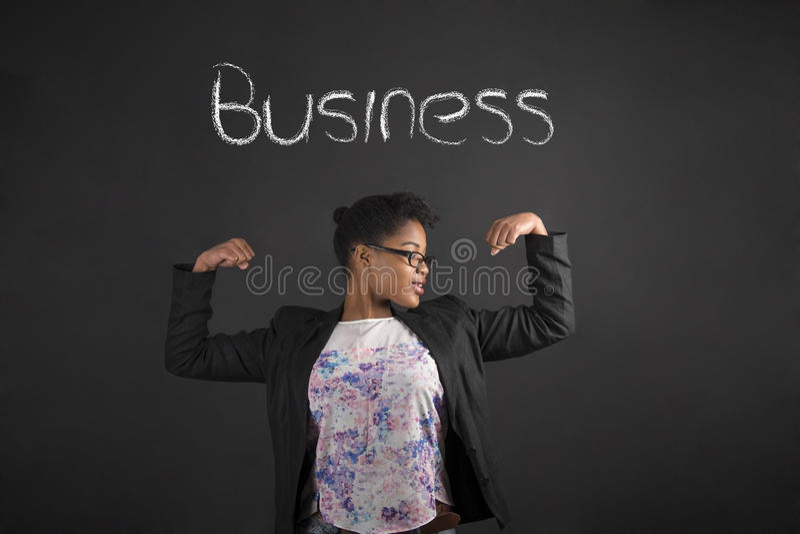Afrikansk kvinna med starka armar för affär på svart tavlabakgrund arkivfoton