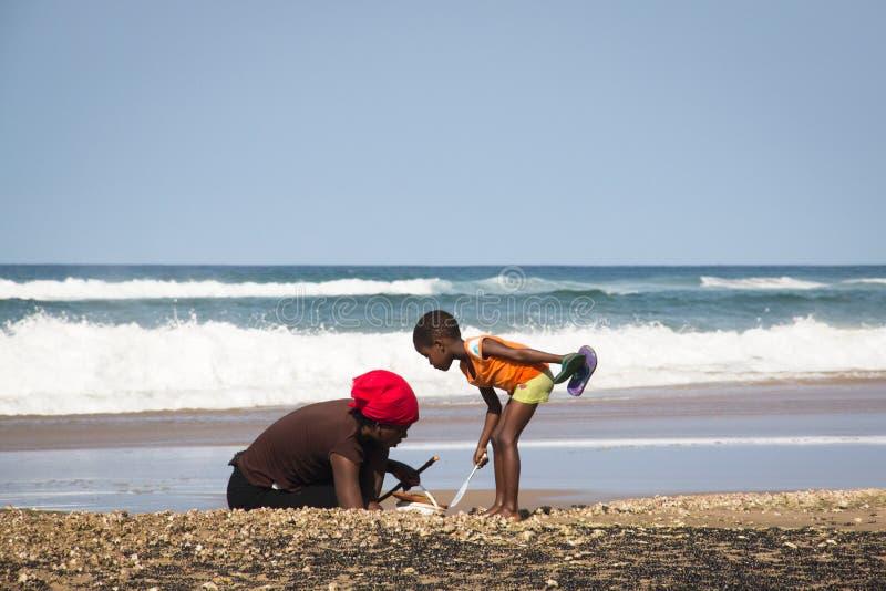 Afrikansk kvinna och barn som fångar krabbor arkivbilder