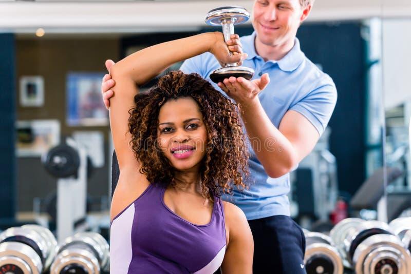 Afrikansk kvinna och instruktör på övningen i idrottshall royaltyfria bilder