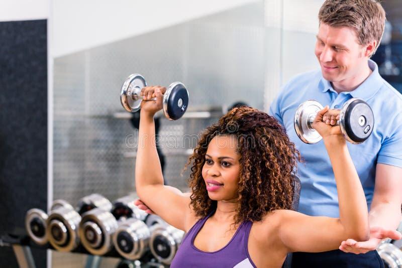 Afrikansk kvinna och instruktör på övningen i idrottshall royaltyfria foton