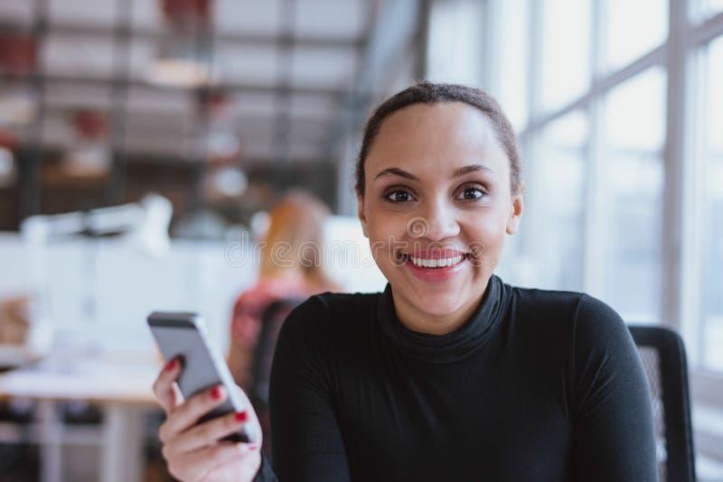 Afrikansk kvinna på arbete som ser att le för kamera arkivbild