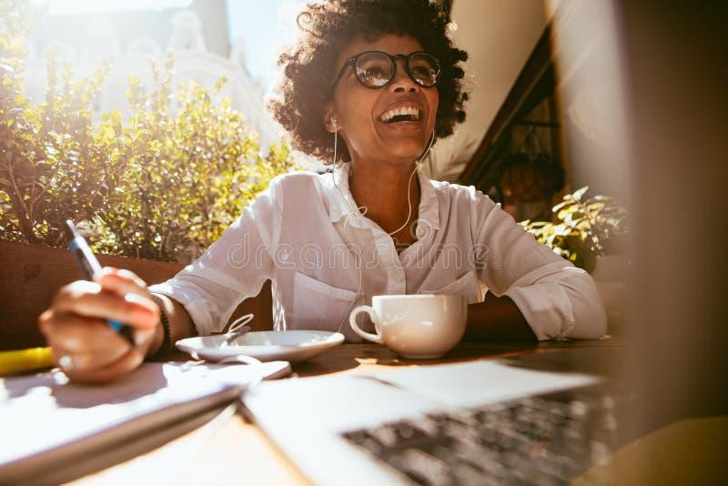 Afrikansk kvinna som arbetar från en coffee shop arkivbilder
