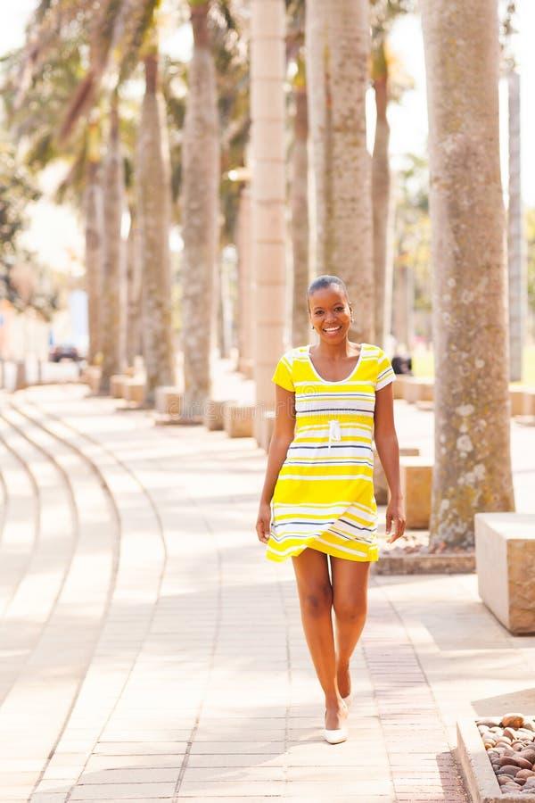 Afrikansk kvinna som går den stads- gatan royaltyfri foto