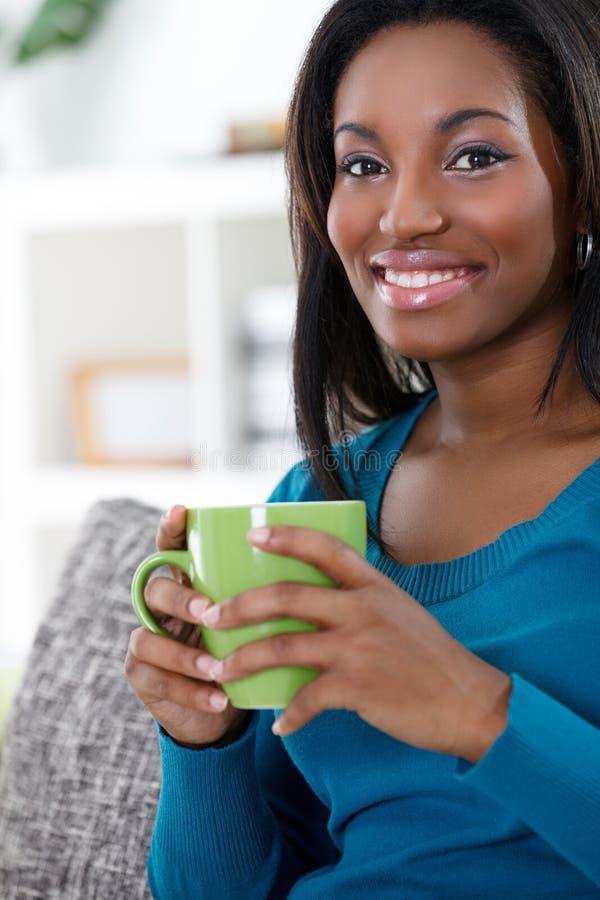 Afrikansk kvinna som tycker om i kaffe arkivfoto