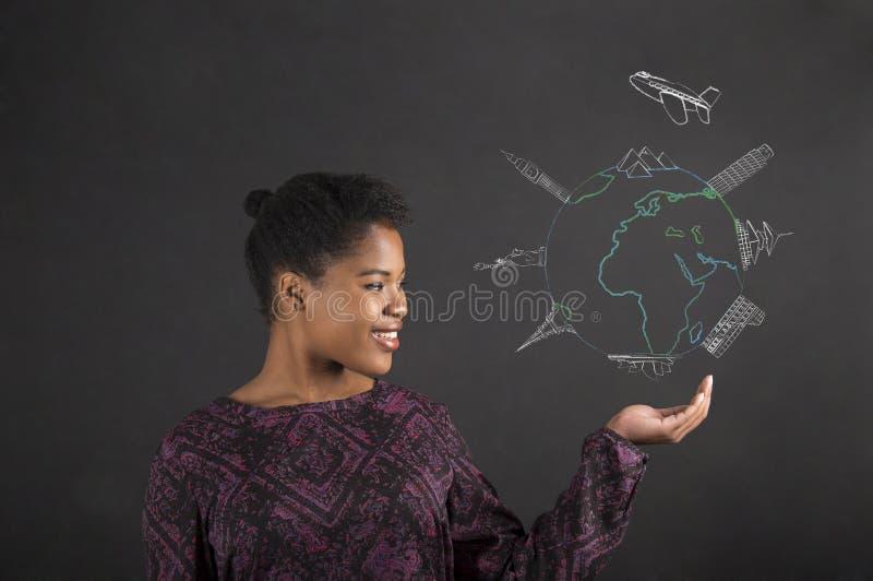 Afrikansk kvinnainnehavhand ut med ett globalt loppdiagram på svart tavlabakgrund fotografering för bildbyråer