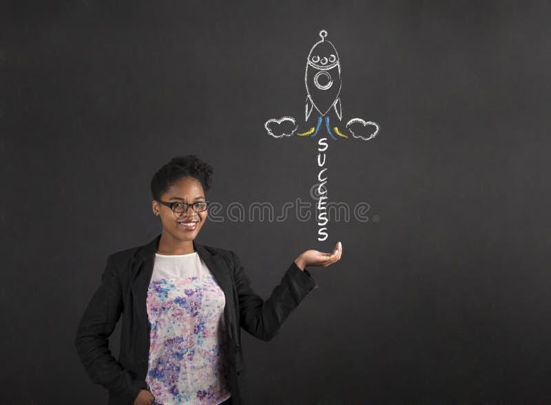Afrikansk kvinnainnehavhand ut med framgångraket på svart tavlabakgrund arkivfoto