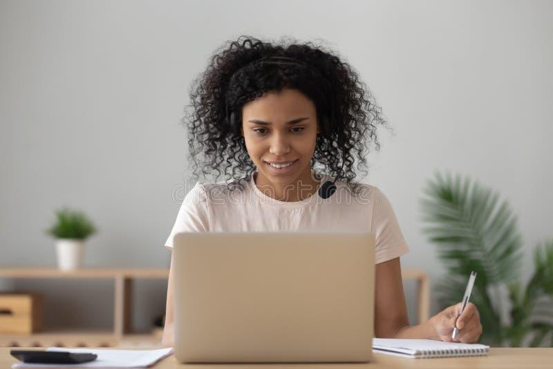 Afrikansk kvinnastudent e som lär göra anmärkningar som ser bärbara datorn royaltyfria foton