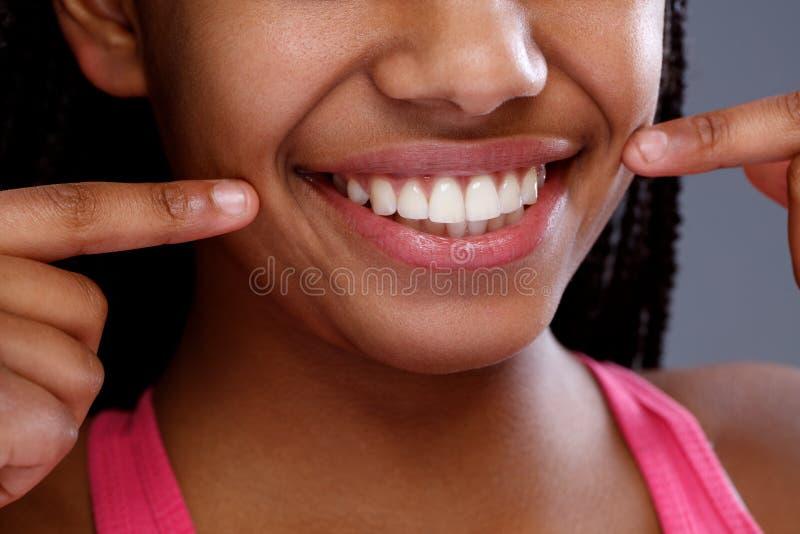 Afrikansk kvinnlig som pekar till hennes tänder, slut upp royaltyfria bilder