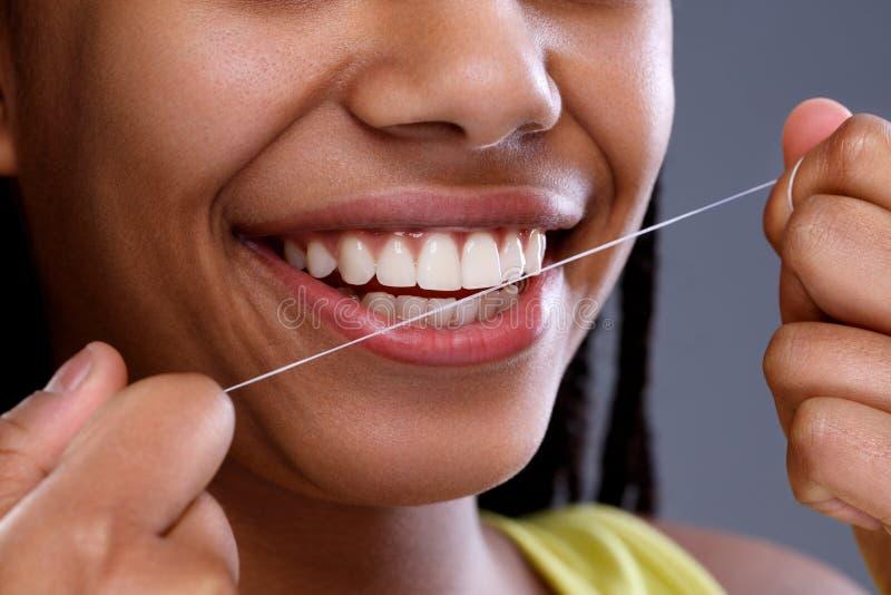 Afrikansk kvinnlig som tar upp omsorg av hennes tänder, slut royaltyfria foton
