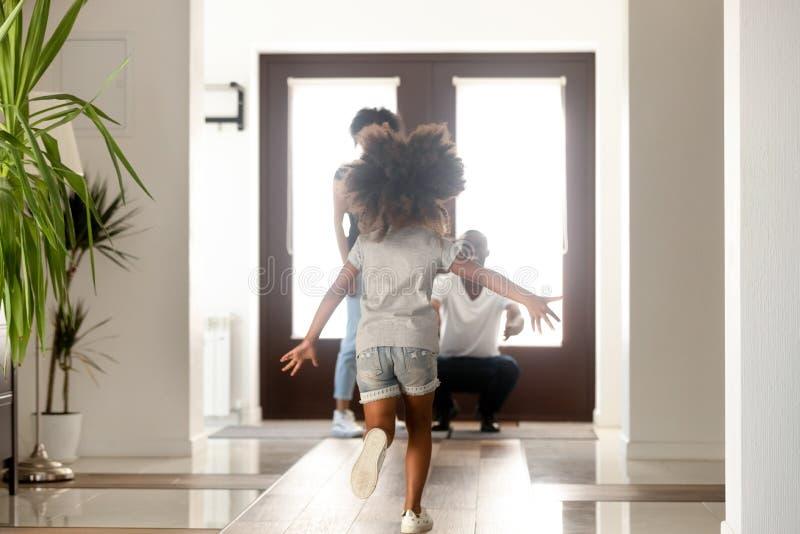 Afrikansk liten dotter som kör till föräldrar som anseende i dörröppning royaltyfria bilder