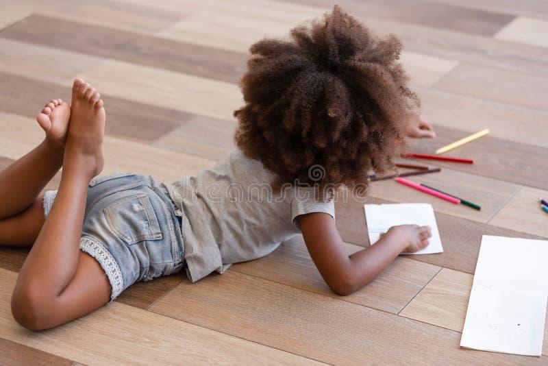 Afrikansk liten flickateckning för tillbaka sikt som ligger på varmt golv royaltyfri fotografi