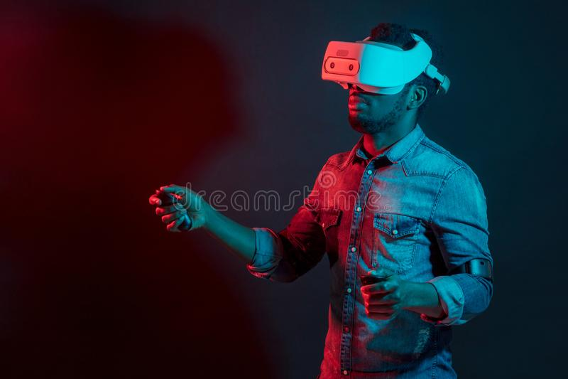 Afrikansk man i vit, b?rande VR-h?rlurar med mikrofon p? r?d och bl? dubbelf?rgbakgrund royaltyfria bilder