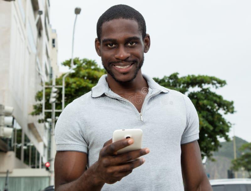 Afrikansk man med skägget som överför meddelandet med telefonen royaltyfri foto