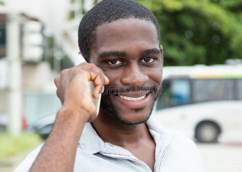 Afrikansk man med skägget som skrattar på telefonen arkivbild
