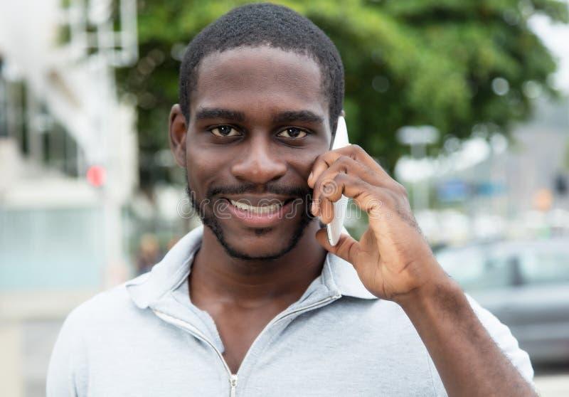Afrikansk man med skägget som talar på telefonen arkivbilder
