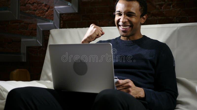 Afrikansk man som är upphetsad för lyckad online-shopping fotografering för bildbyråer