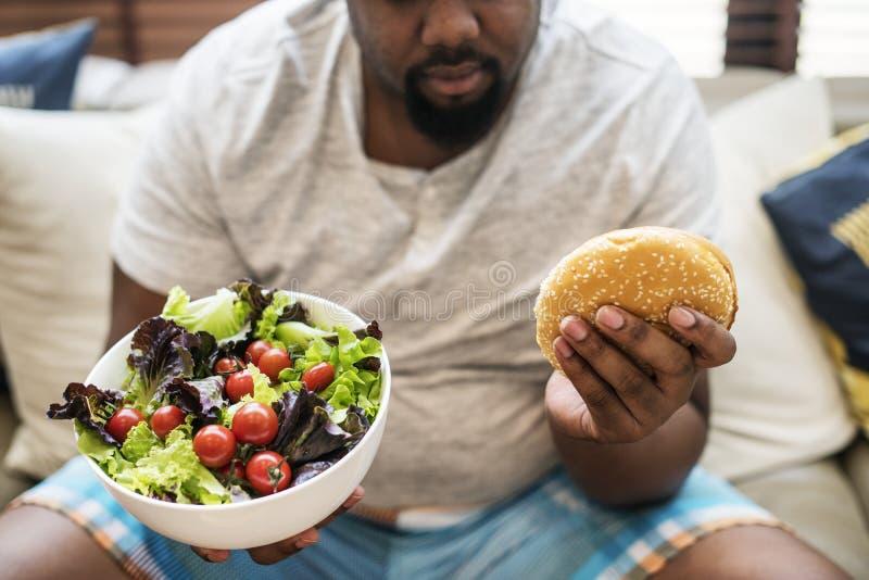 Afrikansk man som äter en stor hamburgare royaltyfri foto