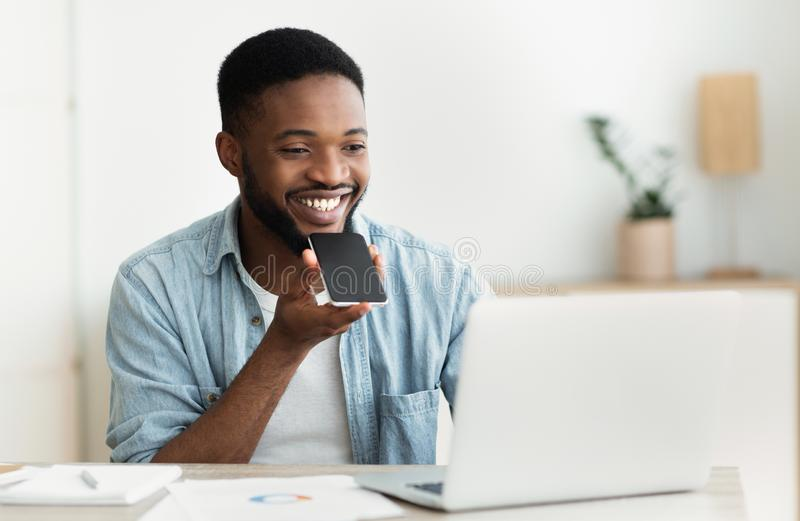 Afrikansk man som använder stämmaassistenten på mobiltelefonen arkivbild