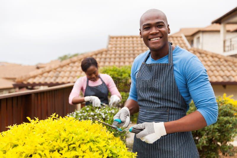 Afrikansk man som arbeta i trädgården frun royaltyfri foto