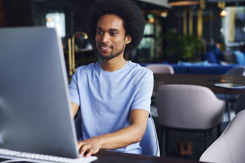 Afrikansk man som arbetar på datoren i kontoret fotografering för bildbyråer
