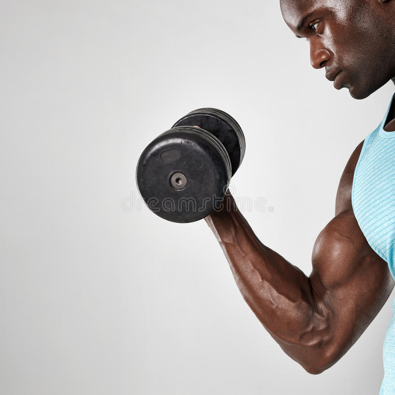 Afrikansk man som gör bicepskrullningen med hanteln royaltyfria bilder
