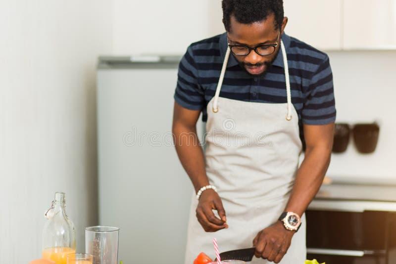 Afrikansk man som hemma förbereder sund mat i kök royaltyfria foton