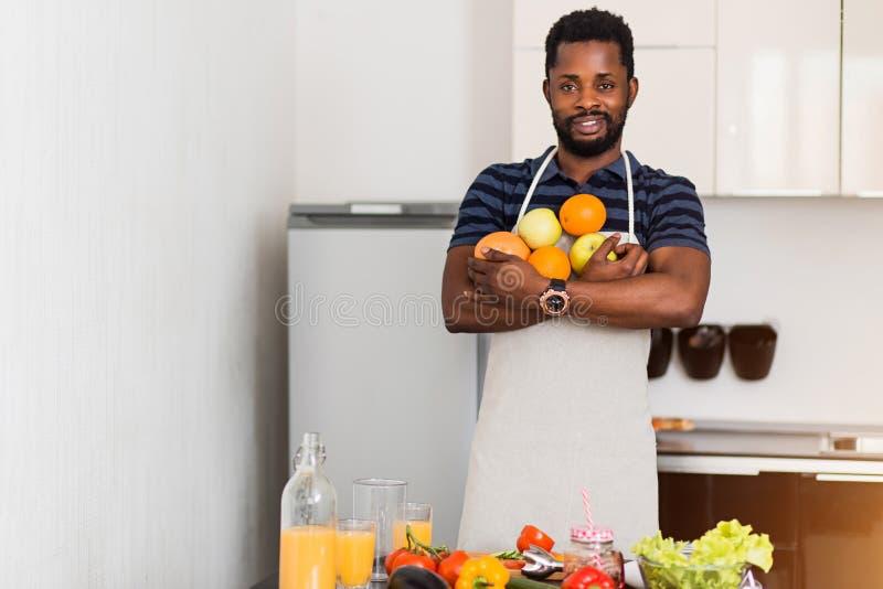 Afrikansk man som hemma förbereder sund mat i kök arkivbild