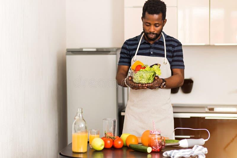 Afrikansk man som hemma förbereder sund mat i kök arkivfoton