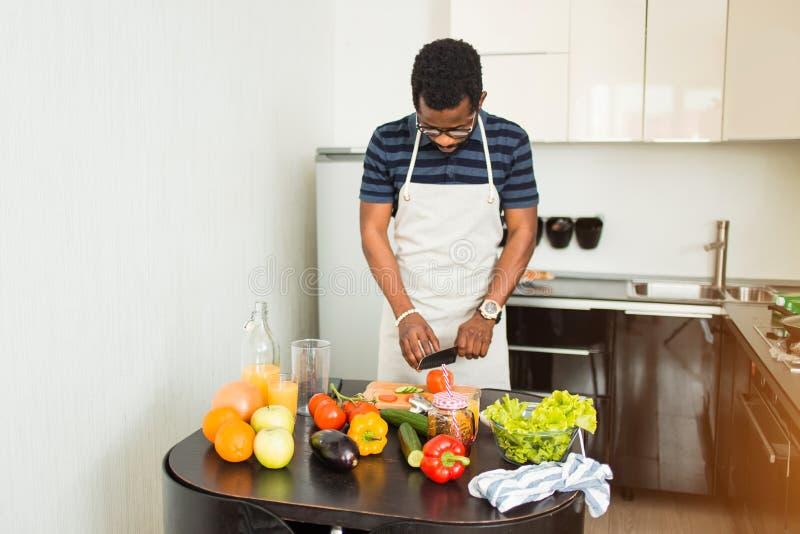 Afrikansk man som hemma förbereder sund mat i kök royaltyfri bild
