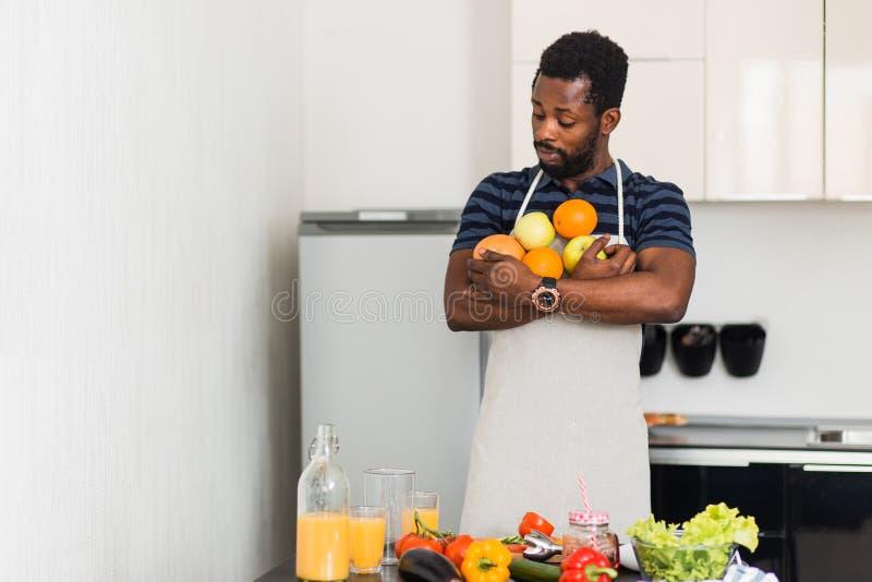 Afrikansk man som hemma förbereder sund mat i kök arkivfoto