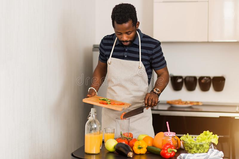 Afrikansk man som hemma förbereder sund mat i kök arkivbilder