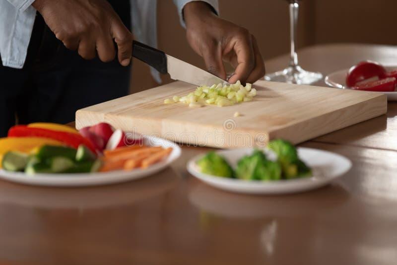 Afrikansk man som hugger av grönsaker som förbereder matställecloseuphänder royaltyfria foton