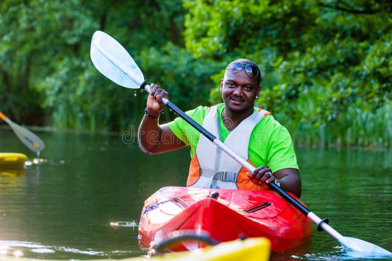 Afrikansk man som paddlar med kanoten på floden royaltyfri fotografi