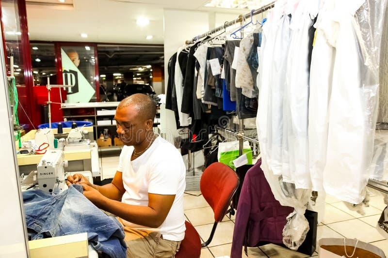 Afrikansk man som reparerar kläder på ett torrt rengöringsmedel fotografering för bildbyråer