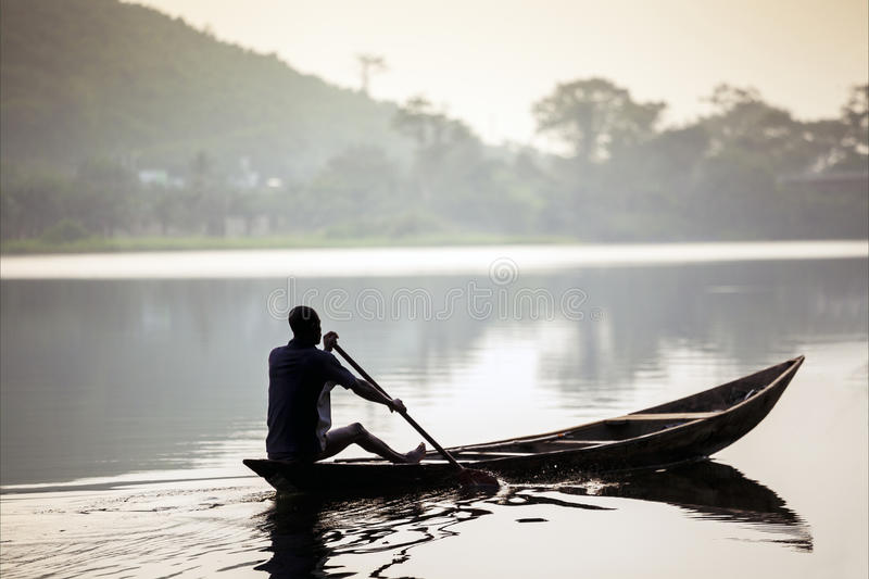 Afrikansk man som rider en kanot royaltyfri foto