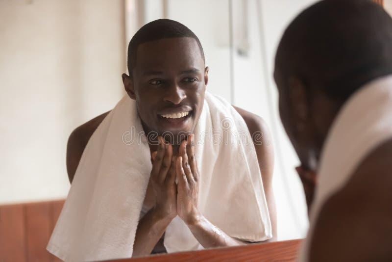 Afrikansk man som ser i spegellokalvårdframsida, når att ha rakat royaltyfria foton